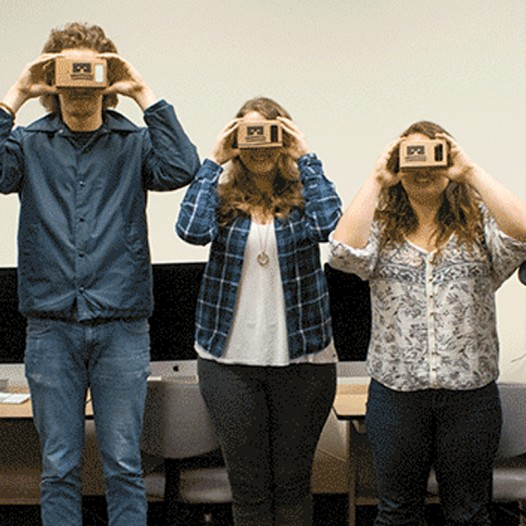 Students hold virtual reality goggles