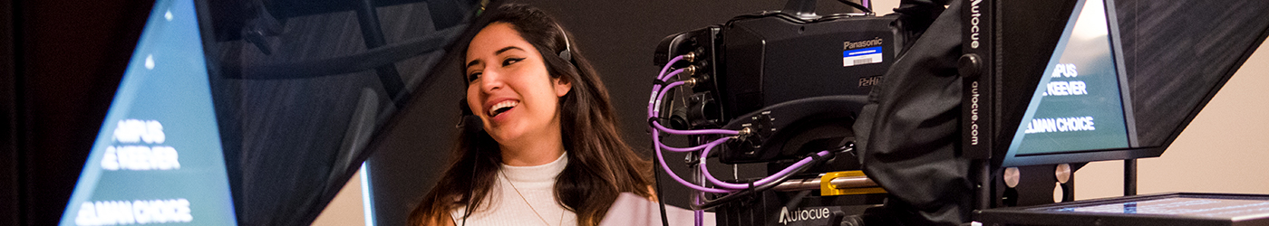 Student laughs and stands behind broadcast equipment in class.