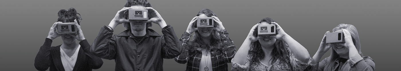 Students holding cardboard virtual reality goggles