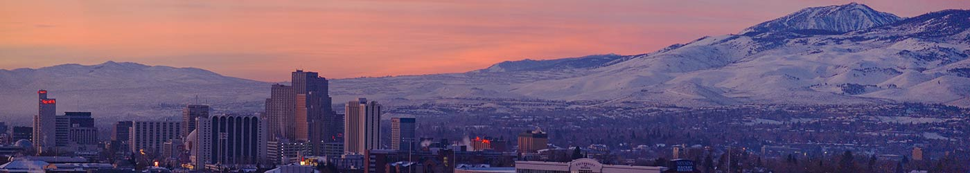 A pink sunrise over snowcapped mountains and the Reno skyline.