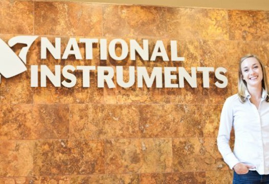 Amee Christian poses in front of National Instruments sign