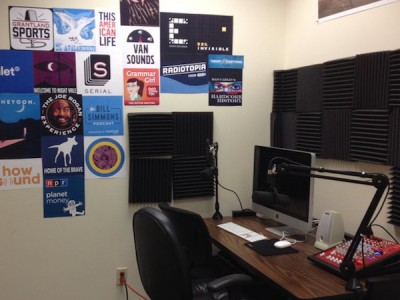 Podcast studio, single desk with two microphones and posters for popular podcasts on the walls
