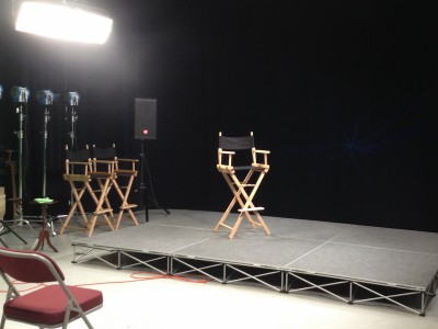 Video studio - black director chair on a stage with bright lights.