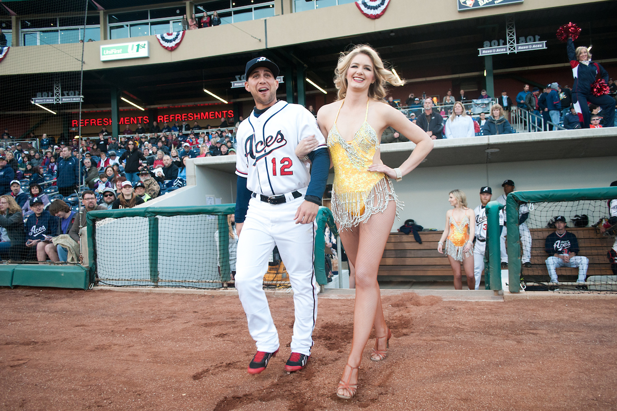 Baseball player and showgirl walk onto a field.
