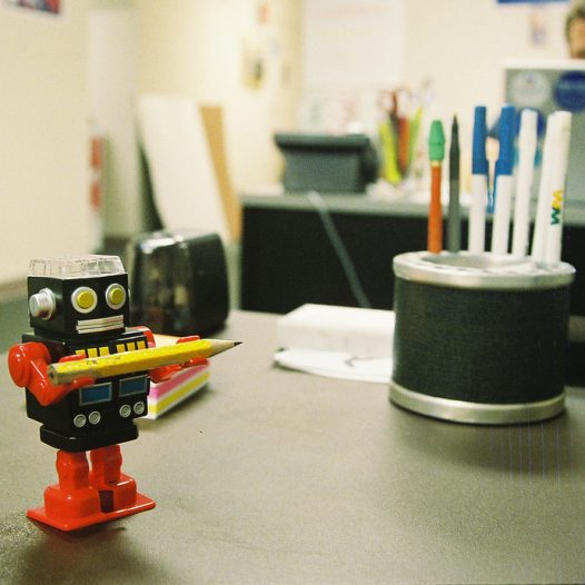 Toy robot holding a pencil on a desk