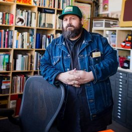 Graphic designer Aaron Draplin poses in front of bookcase.