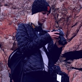 Student looks through photos on DSLR camera.