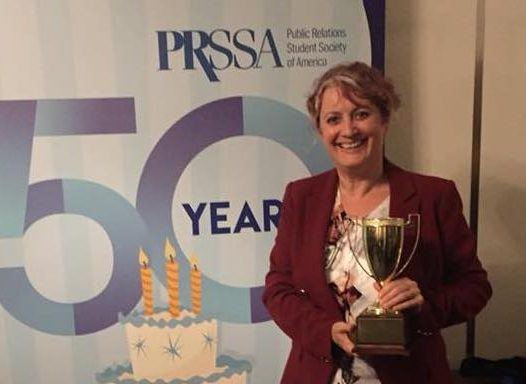 Alison Gaulden holding a trophy in front of a PRSSA banner.