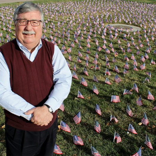 Bob Felten stands by more than 2,000 flags placed every year in front of the Joe Crowley Student Union.