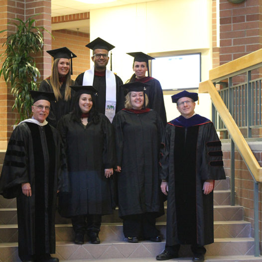 The graduating class of the winter 2017 cohort of graduate students poses for a photo.