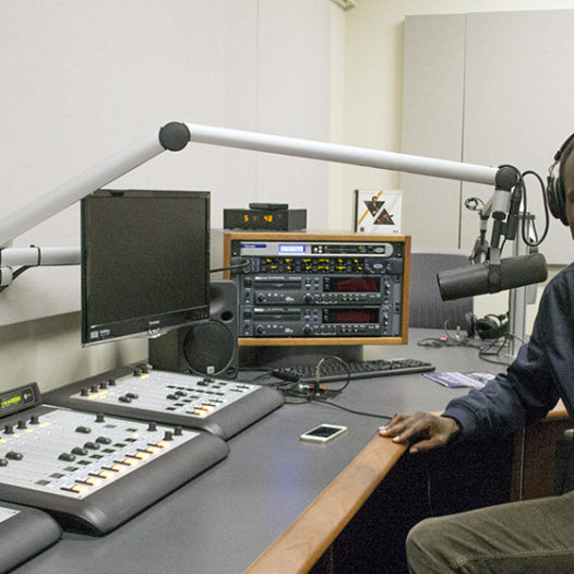 Prince Nesta, a former radio host in Kenya and current graduate student at the Reynolds School of Journalism, poses for a photo in a podcasting studio.