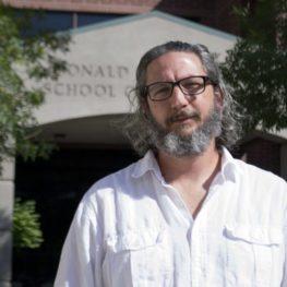Professor Ezequiel Korin poses in front of the Reynolds School of Journalism.
