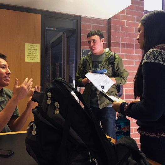Professor Myrt Running Wolf talks to two students in classroom.