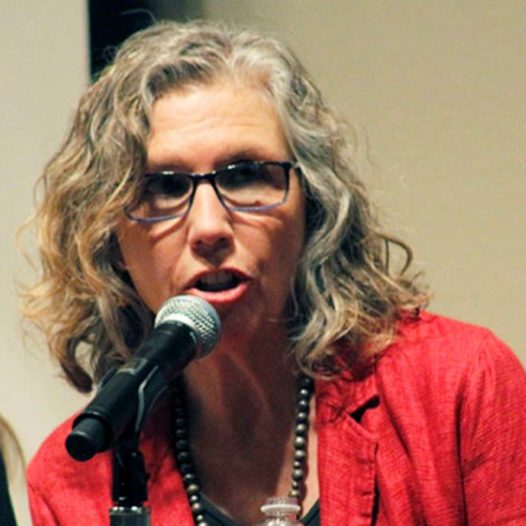 Woman speaks at a microphone.