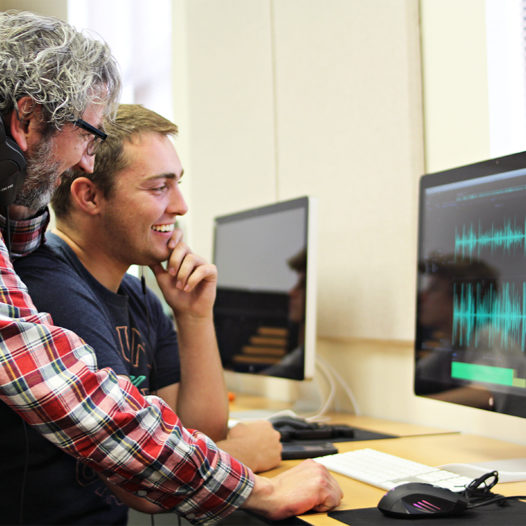 Ezequiel Korin sits with student at computer with sound waves on the screen