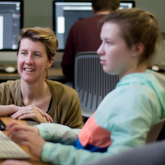 Professor Katherine Hepworth guides a student through a design project in a classroom setting.