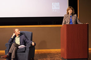 A woman speaks at a podium and a man looks up at her from a chair.