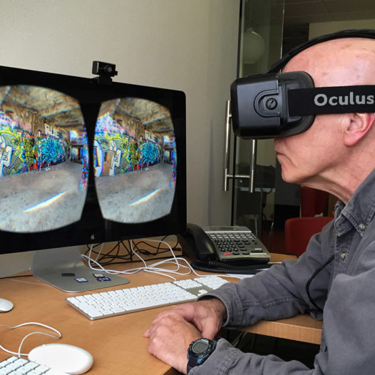 A man sits at a double screen wearing a virtual reality headset.