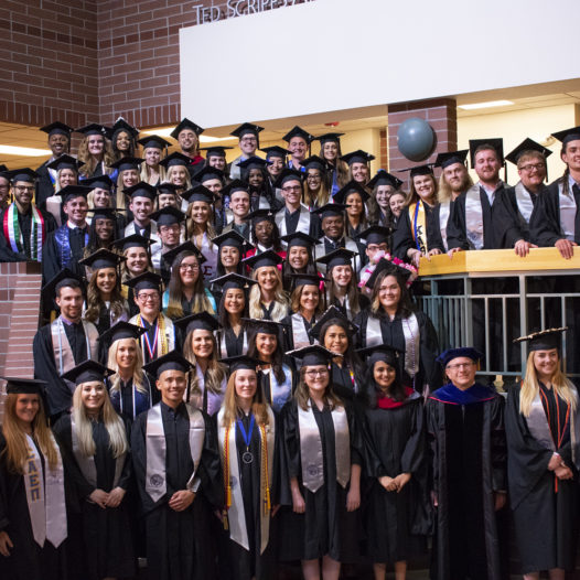 A group of 94 college graduates pose for a photo in their regalia.