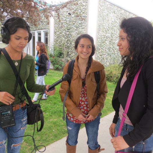 Student interviews two other women outdoors.