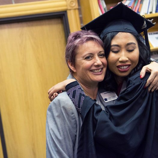Person in graduation cap and gown hugs professor