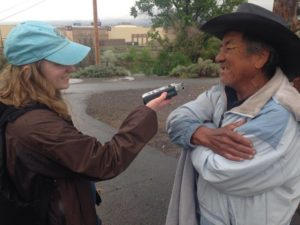 A young woman interviews an older man in wide brimmed hat with an audio recorder.