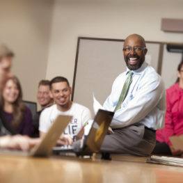 Professor sits on desk near students.
