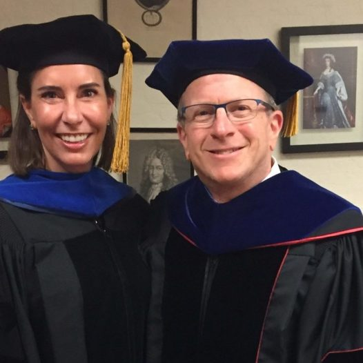 Two people stand indoors in commencement regalia