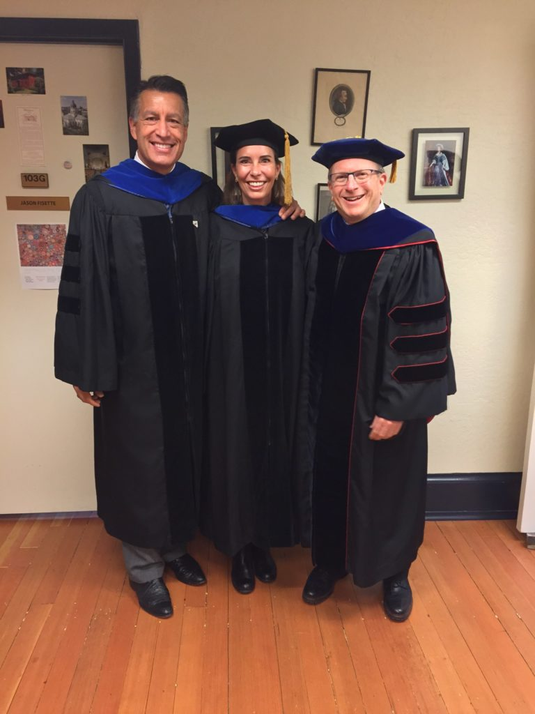 Three people stand indoors in commencement regalia.