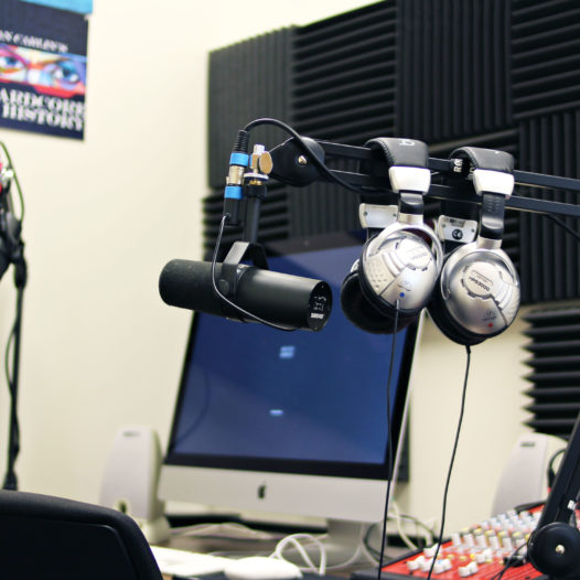 Microphone with headphones hanging and computer and soundboard in background of podcasting room