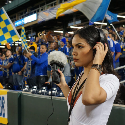 Student collects natural radio sound at a soccer game.