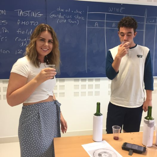 Two students taste wine at a table inside a classroom.