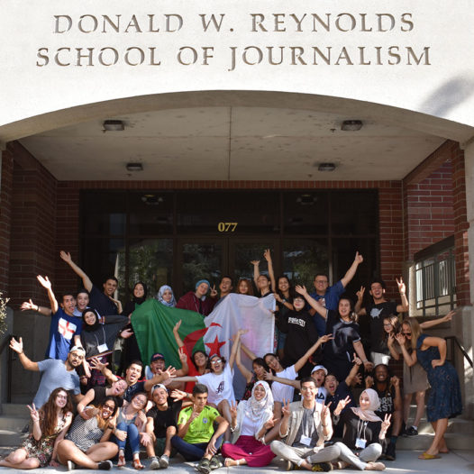 Students pose in a group in front of the Reynolds School.