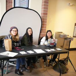 Students sit behind table.