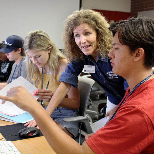 Faculty member advises student at a computer in the Reynolds School.