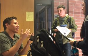 Man speaks with two students.