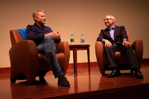 Two men sit on stage and talk.