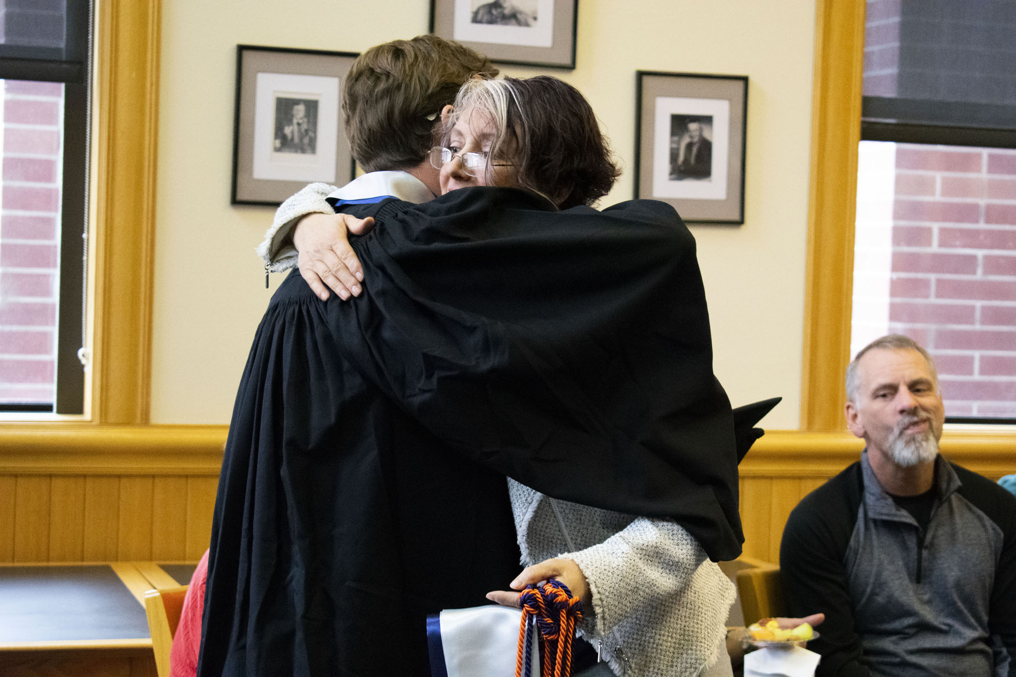 A woman hugs a male student.