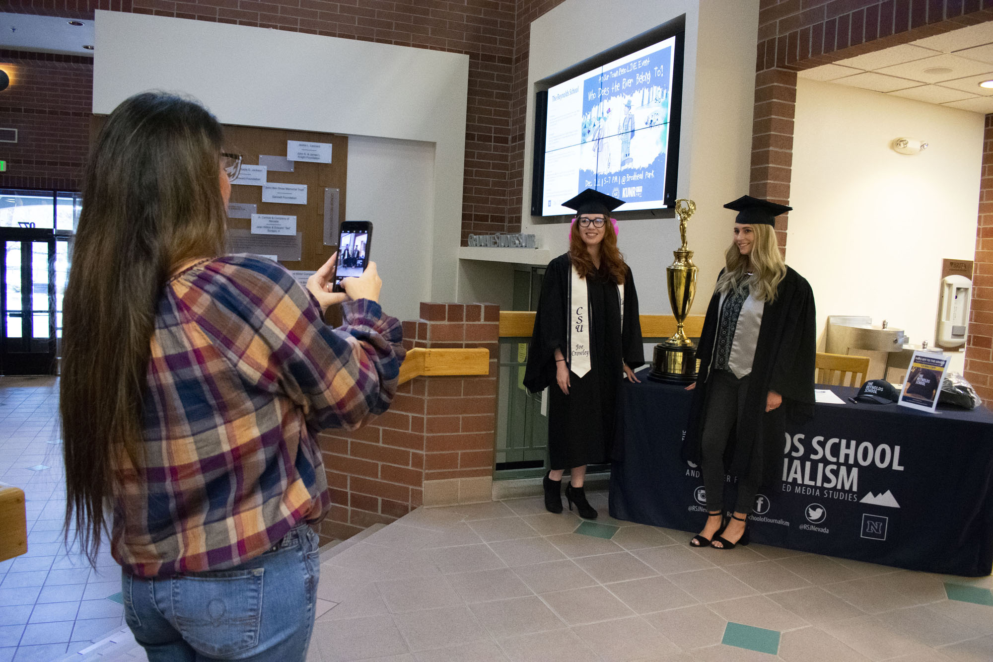 A woman takes a photo of two students.