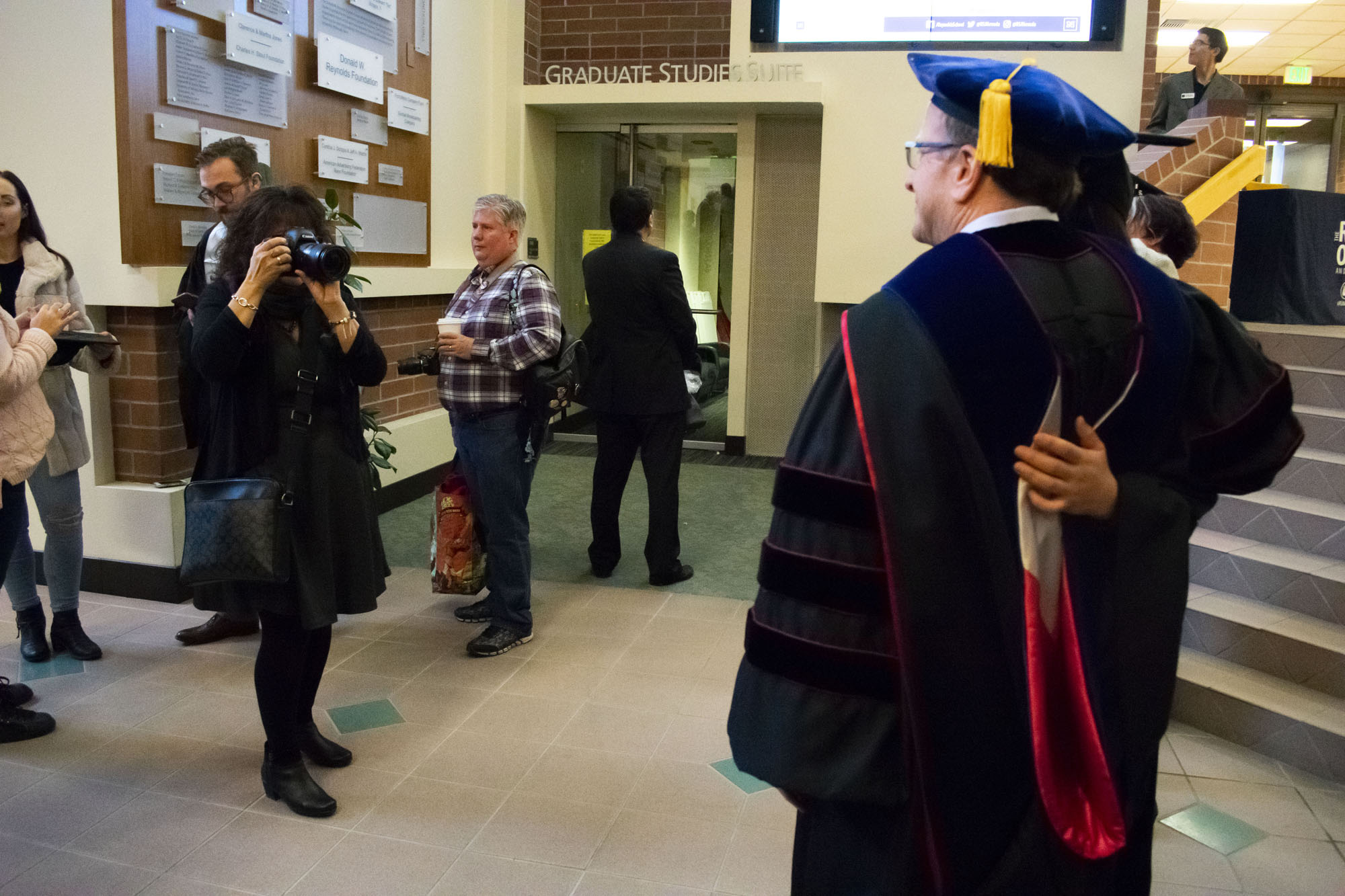A woman takes a photo of a man and a woman in graduation robes.