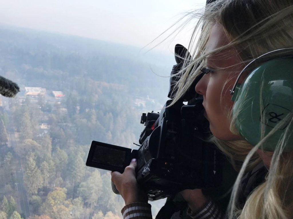 Woman holds a video camera in a helicopter above a forest.