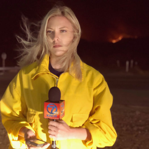 Woman stands holding a microphone in front of a fire burning on a hill.