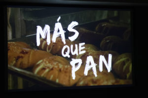 """A still from the film """"Mas Que Pan."""" The title is seen over a tray of bread."""