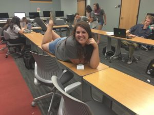 Student lies on desk and poses for the camera during JFIT.