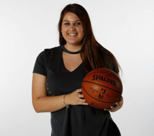 Woman poses with a basketball for the camera against white backdrop.