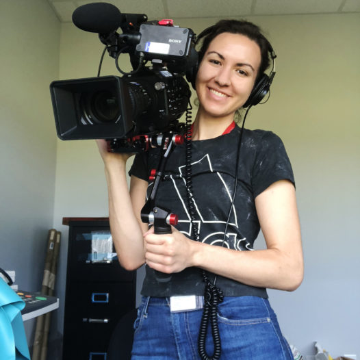 Woman poses with camera.