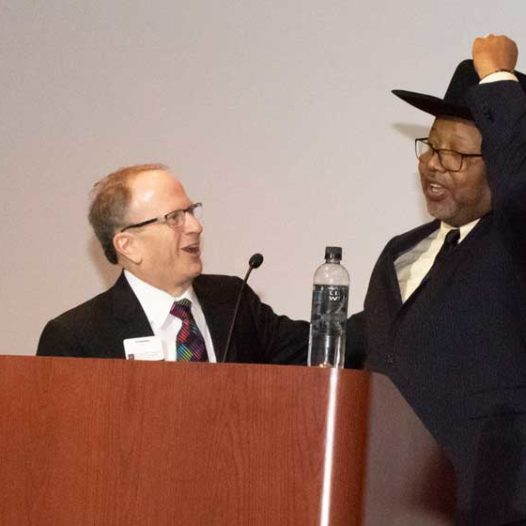 Two men on a stage, one of which putting on a cowboy hat.